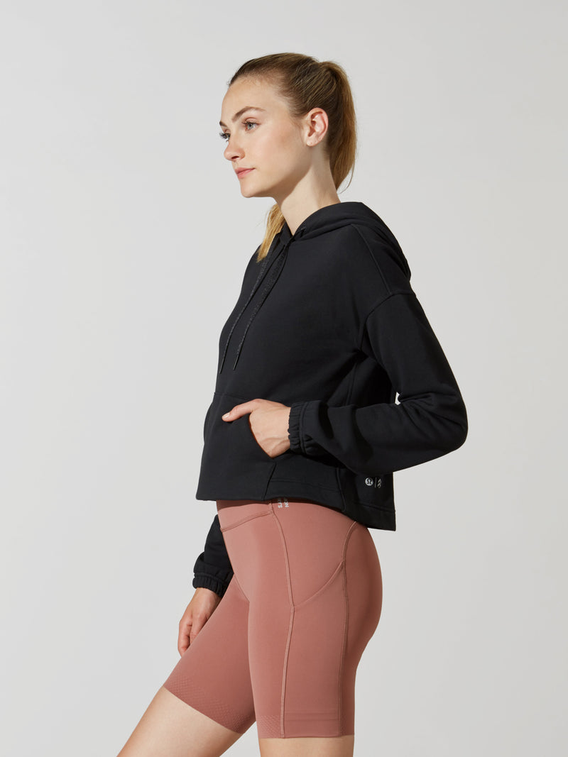 side view of model in black cropped long sleeve hoodie and mauve athletic biker shorts