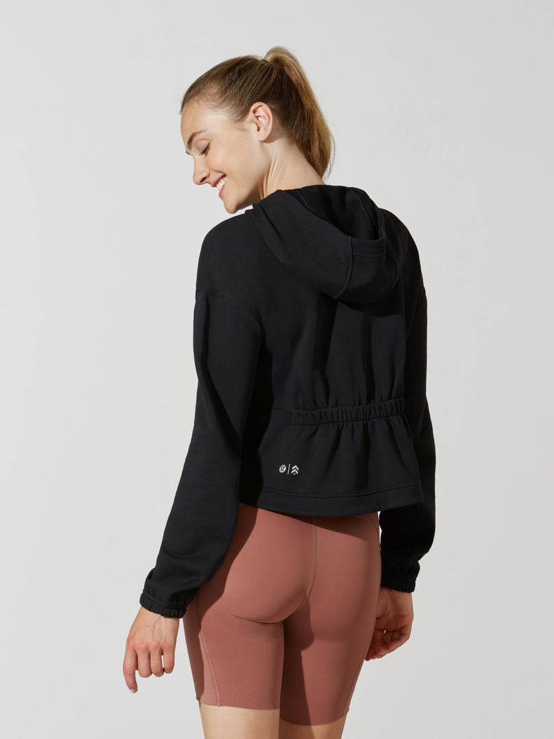 back view of model in black cropped long sleeve hoodie and mauve athletic biker shorts