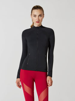 front view of female model in tight black long sleeve athletic jacket and bright red leggings with mesh detail on thigh
