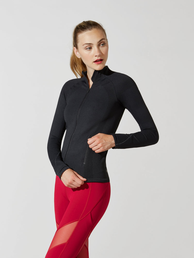 side view of female model in tight black long sleeve athletic jacket and bright red leggings with mesh detail on thigh