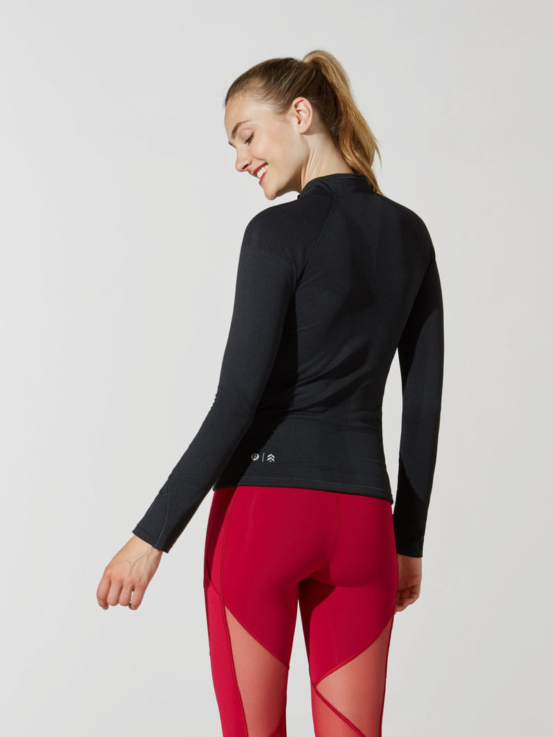 back view of female model in tight black long sleeve athletic jacket and bright red leggings with mesh detail on thigh