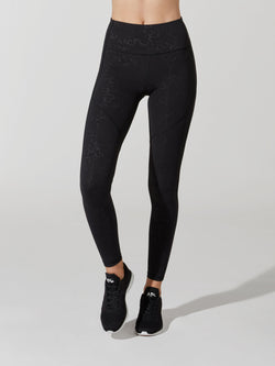 front view of female model in black leggings with embossed shiny detailing and black sneakers