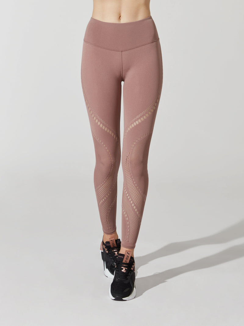 front view of female model in mauve leggings with cutout detailing on thigh and calves and sneakers