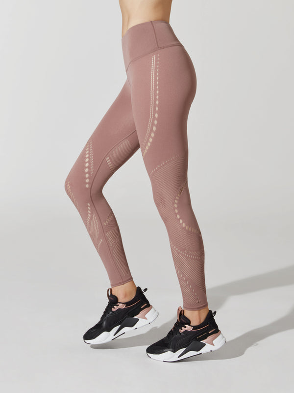 side view of female model in mauve leggings with cutout detailing on thigh and calves and sneakers