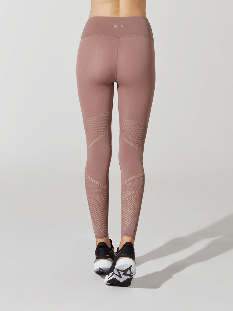 back view of female model in mauve leggings with cutout detailing on thigh and calves and sneakers