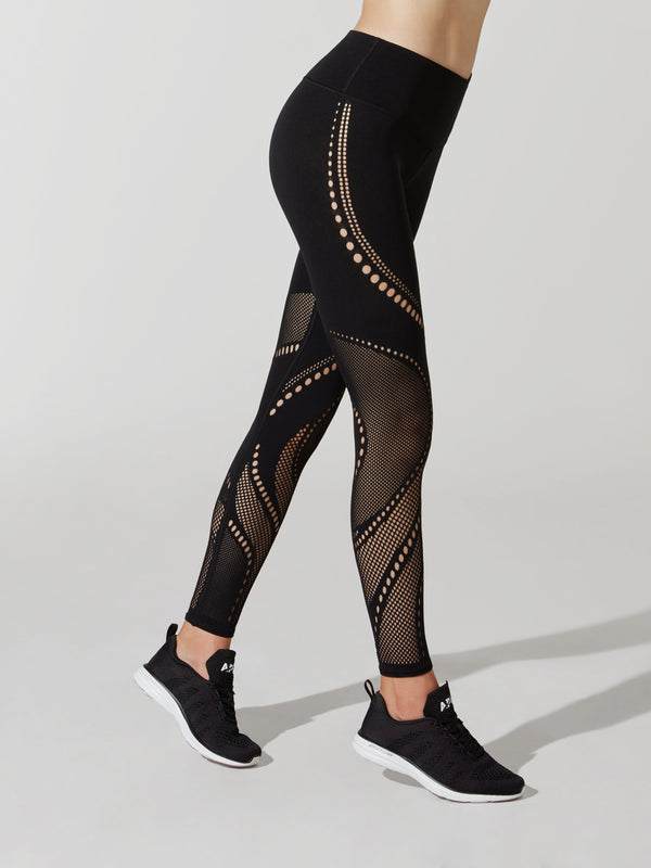 side view of female model in black leggings with cutout detailing on thigh and calves and sneakers