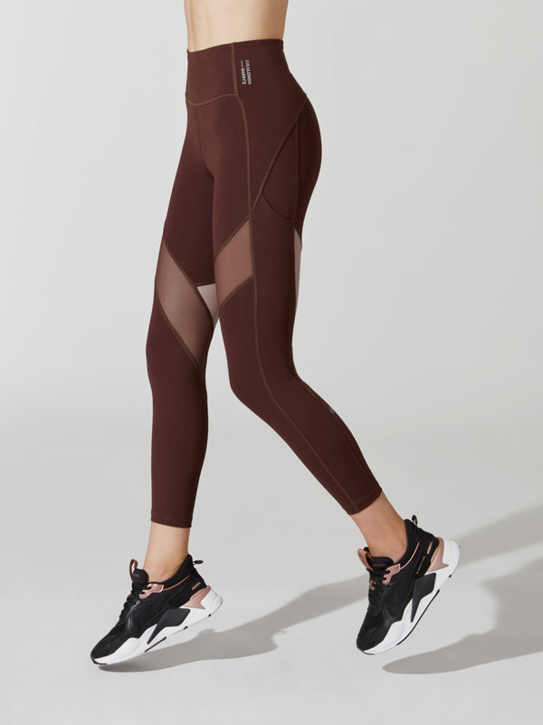 side view of female model in maroon leggings with mesh cutouts on thighs and maroon and pink sneakers