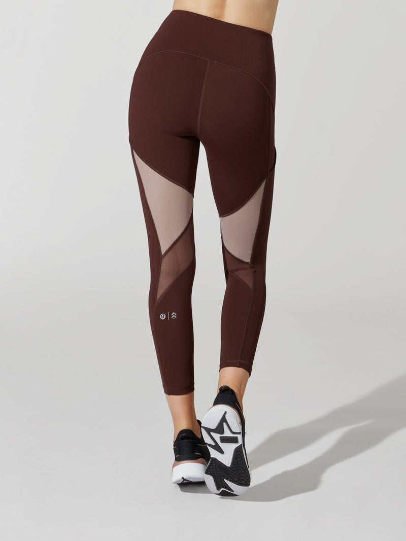 back view of female model in maroon leggings with mesh cutouts on thighs and maroon and pink sneakers