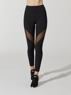 front view of female model in black leggings with mesh cutout on thigh and black sneakers