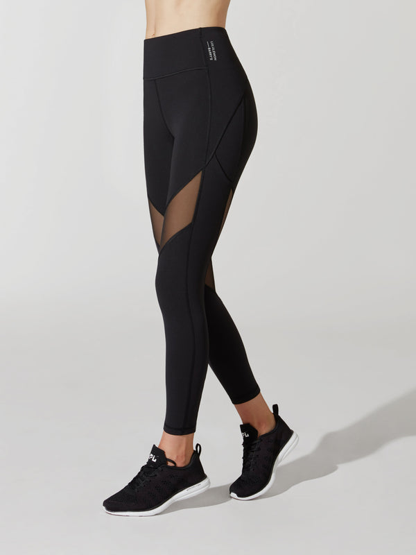 side view of female model in black leggings with mesh cutout on thigh and black sneakers