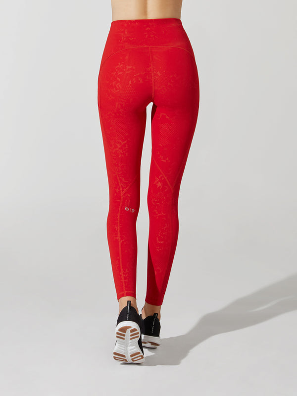 back view of female model in bright red leggings with embossed shiny detailing and black sneakers