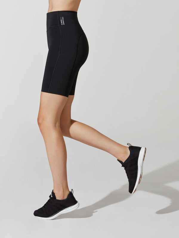 side view of female model in black athletic biker shorts and black sneakers