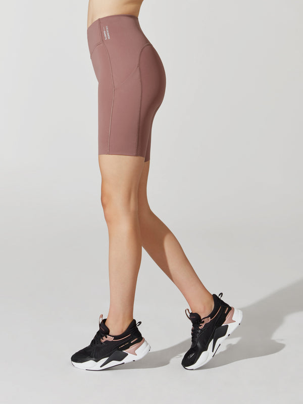 side view of female model in mauve athletic biker shorts and black sneakers
