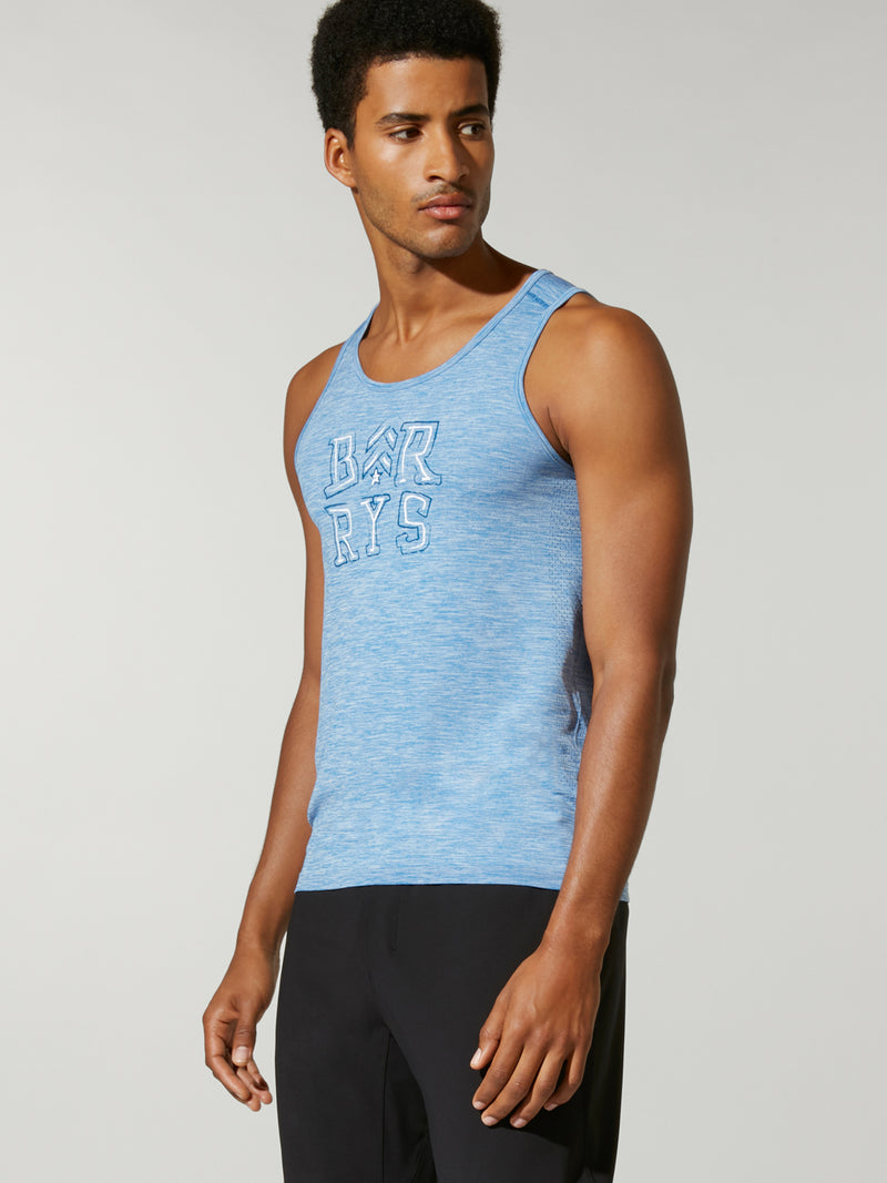 side view of male model in light blue tank top with Barry's written on chest and black shorts