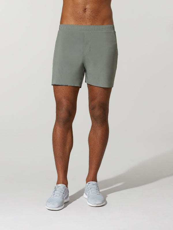 front view of shirtless male model in grey shorts and light grey sneakers