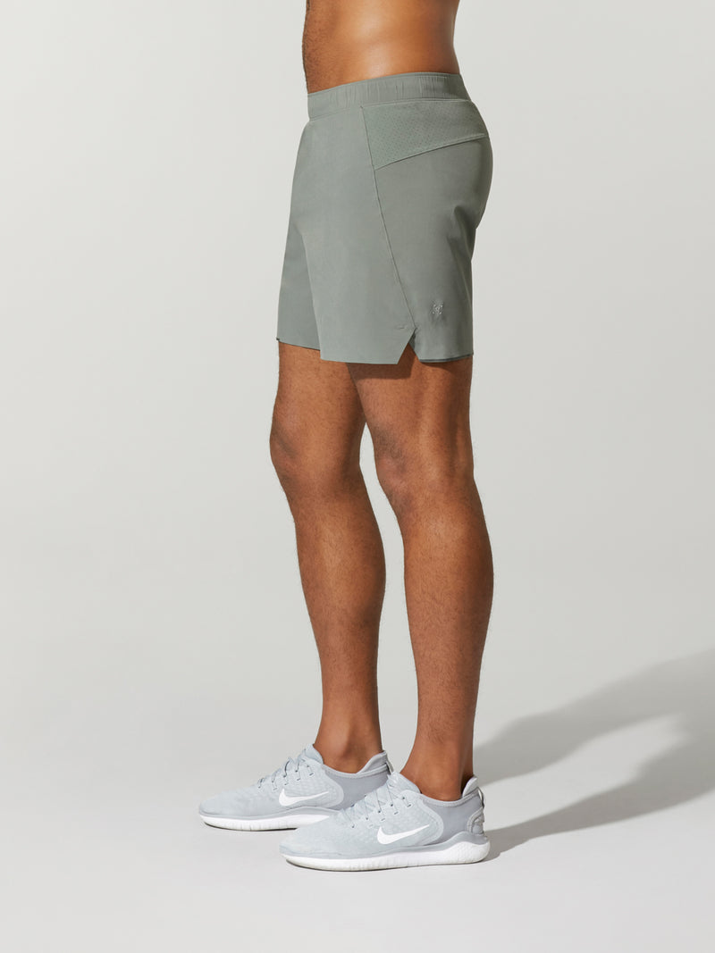 side view of shirtless male model in grey shorts and light grey sneakers