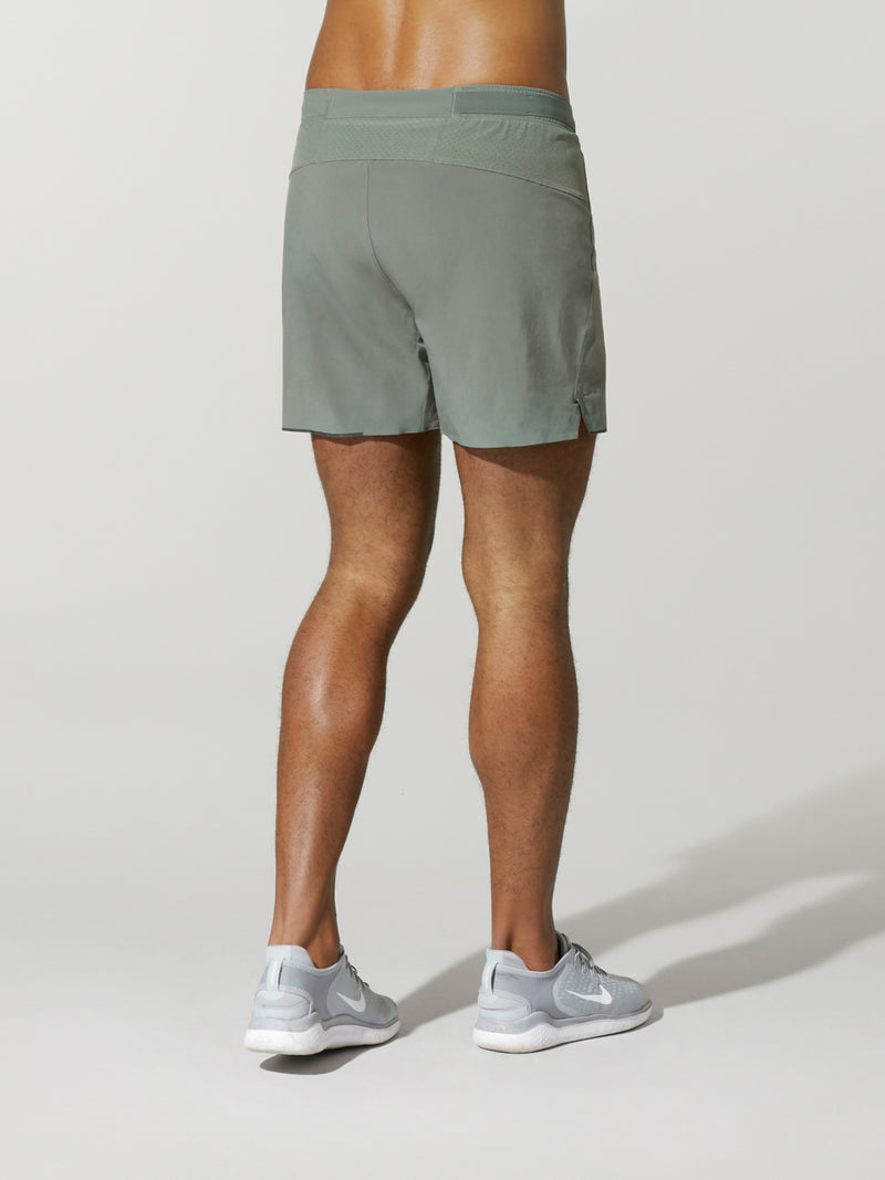 back view of shirtless male model in grey shorts and light grey sneakers