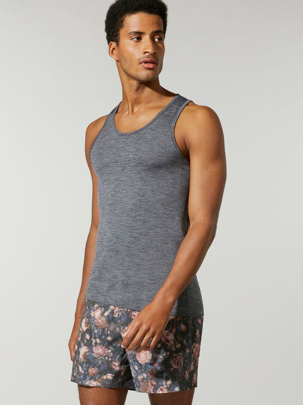 front view of male model in heather grey tank top and pink white and grey patterned shorts