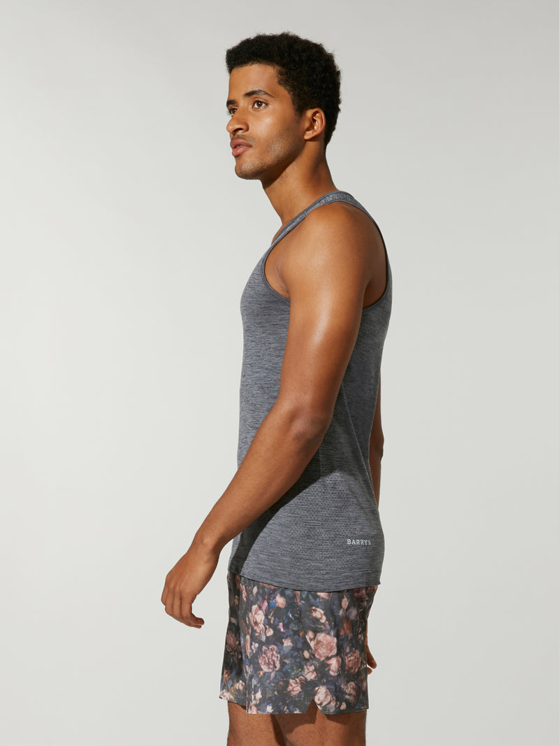 side view of male model in heather grey tank top and pink white and grey patterned shorts