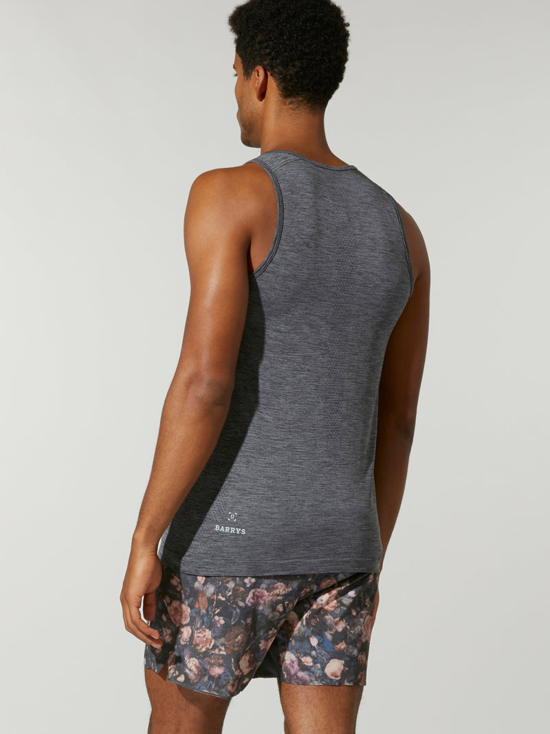 back view of male model in heather grey tank top and pink white and grey patterned shorts