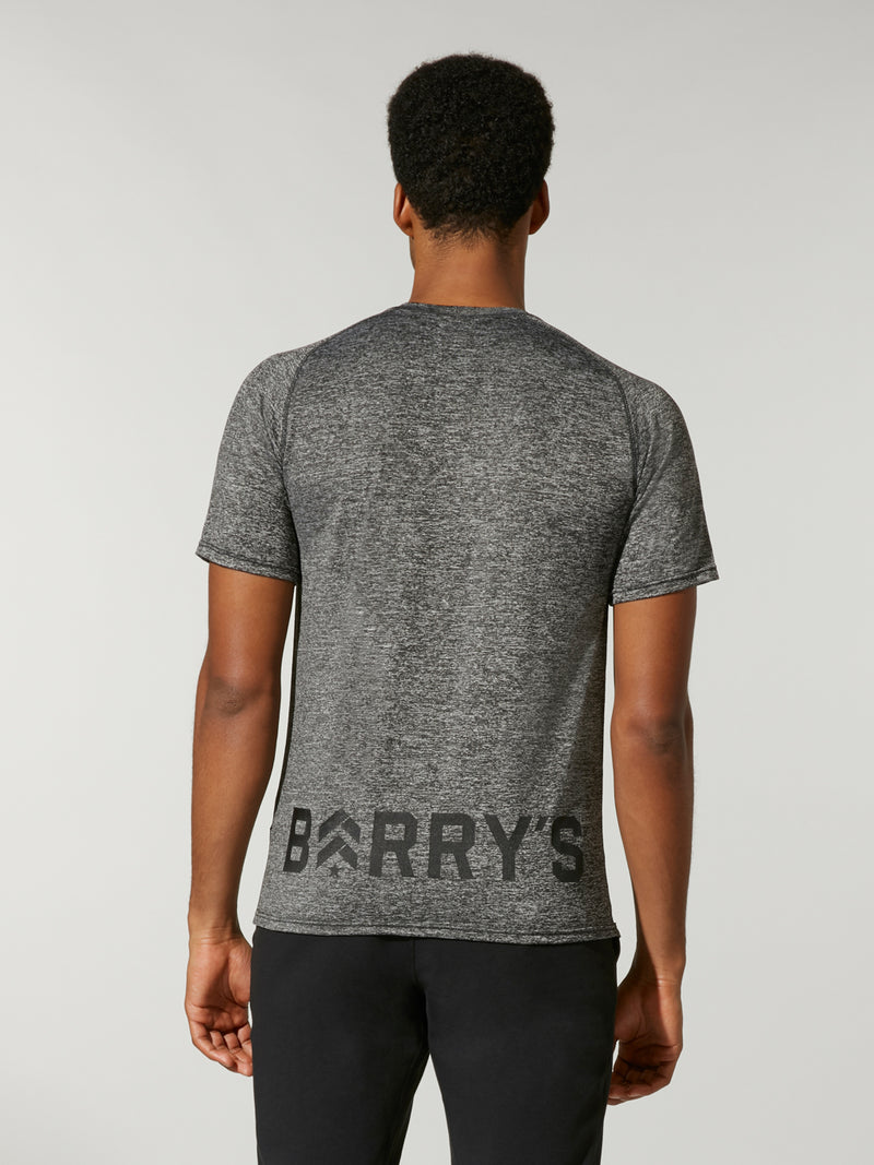 back shot of model  wearing dark heather grey FIT STORM A/C TEE with Barry's logo on bottom