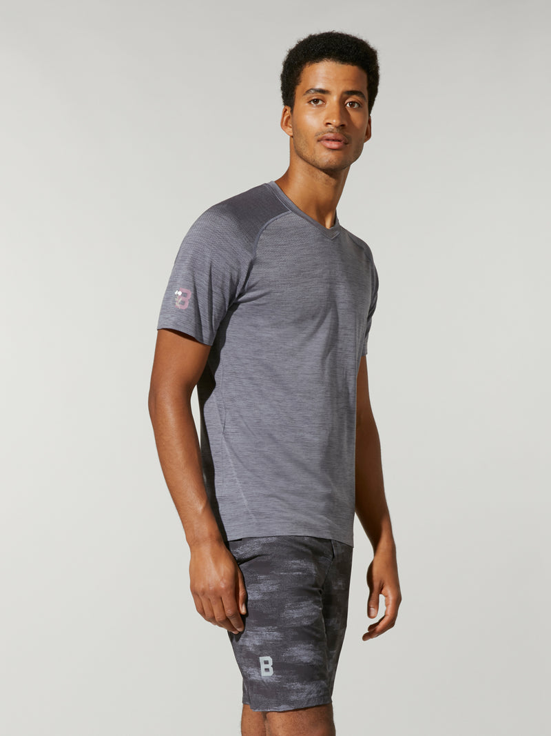 side view of male model in grey t-shirt and grey camouflage shorts