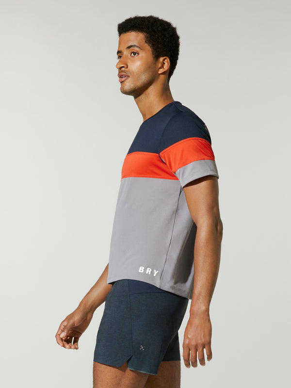 Side shot of model wearing Grey, Orange, and Navy wide striped FOURLAPS X BARRY'S SMASH TEE
