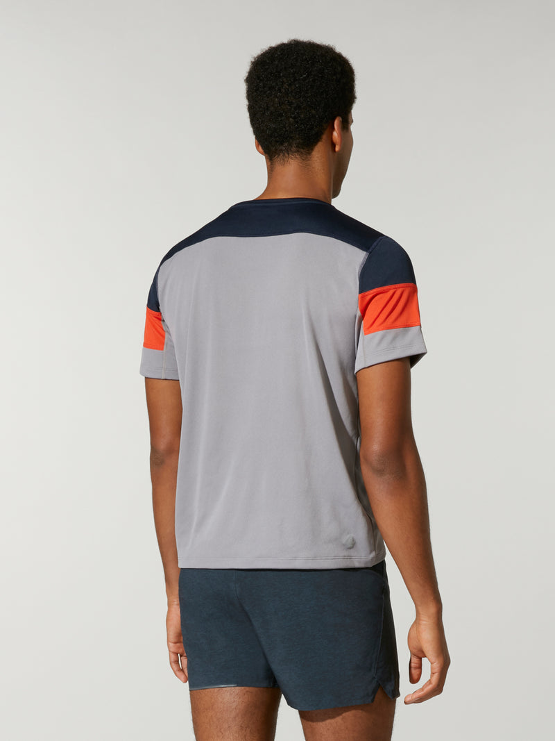 back shot of model wearing Grey, Orange, and Navy wide striped FOURLAPS X BARRY'S SMASH TEE