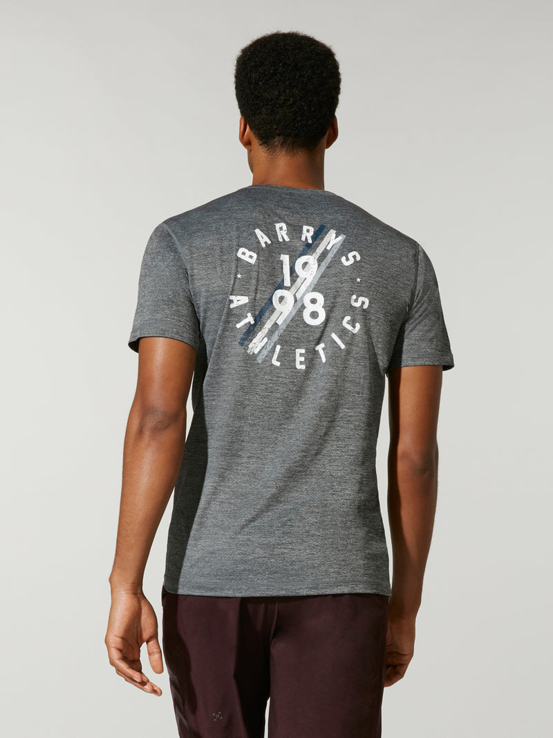 back view of male model in grey athletic t-shirt with white barry's bootcamp logo on back and black shorts