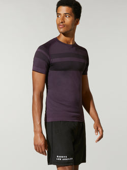 Side shot of model wearing purple FIT NIGHTSHADE SEAMLESS TEE with dark stripe across chest