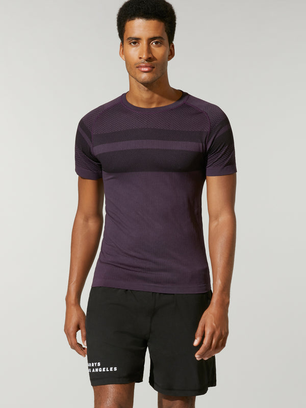 front shot of model wearing purple FIT NIGHTSHADE SEAMLESS TEE with dark stripe across chest