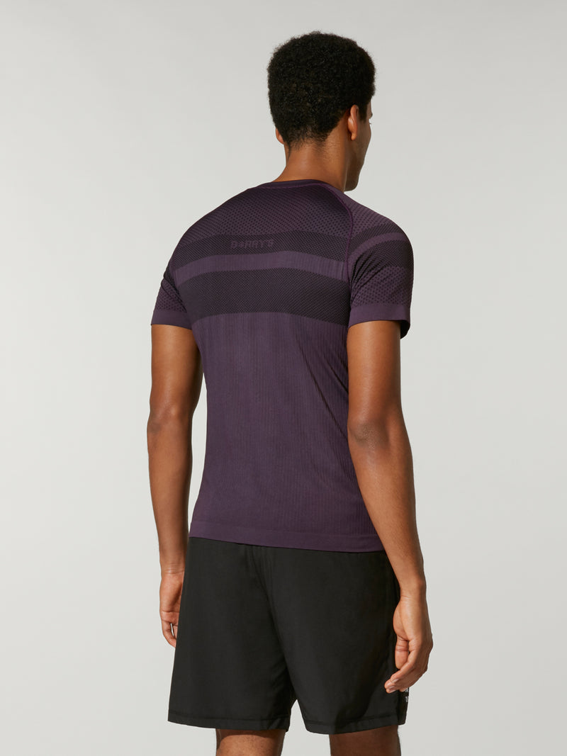 back shot of model wearing purple FIT NIGHTSHADE SEAMLESS TEE with dark stripe across back
