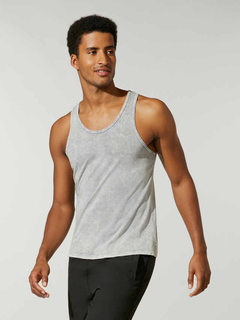 side view of male model in light grey tank top and black athletic shorts