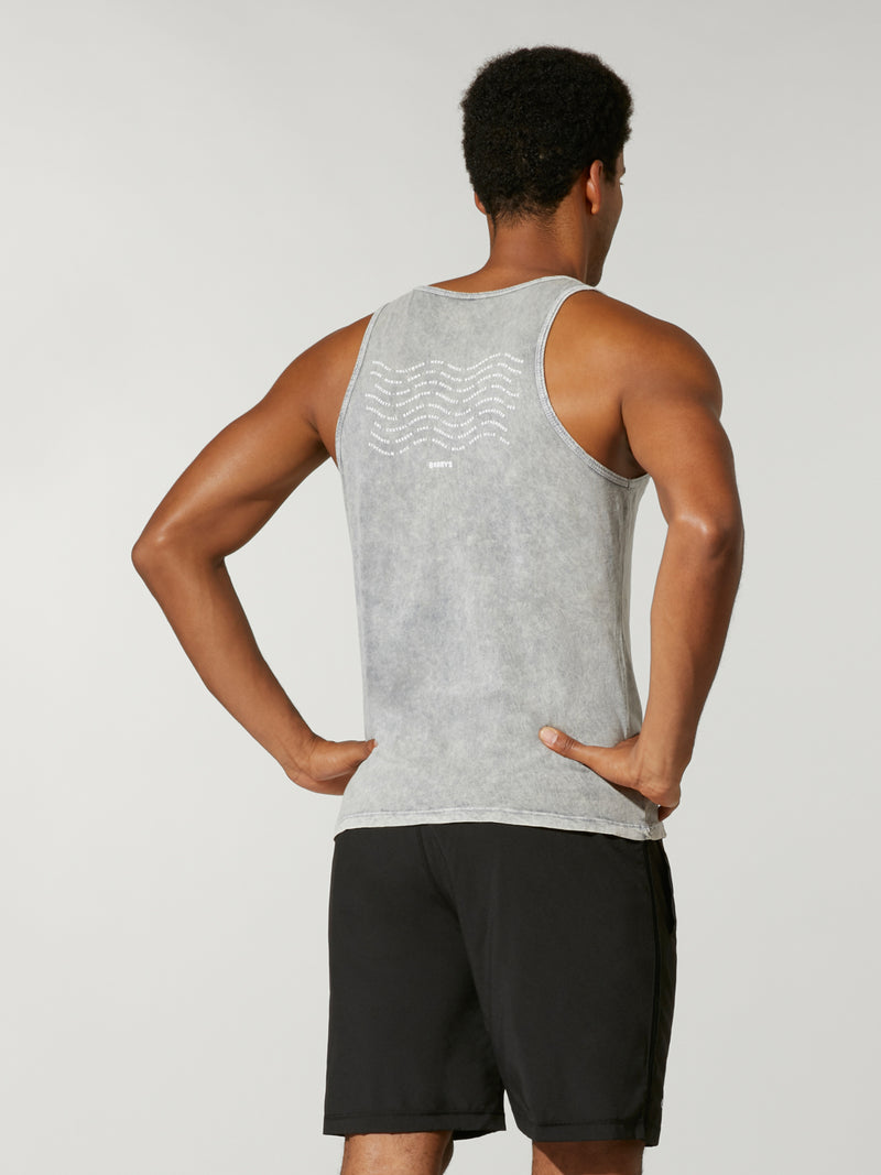 back view of male model in light grey tank top and black athletic shorts