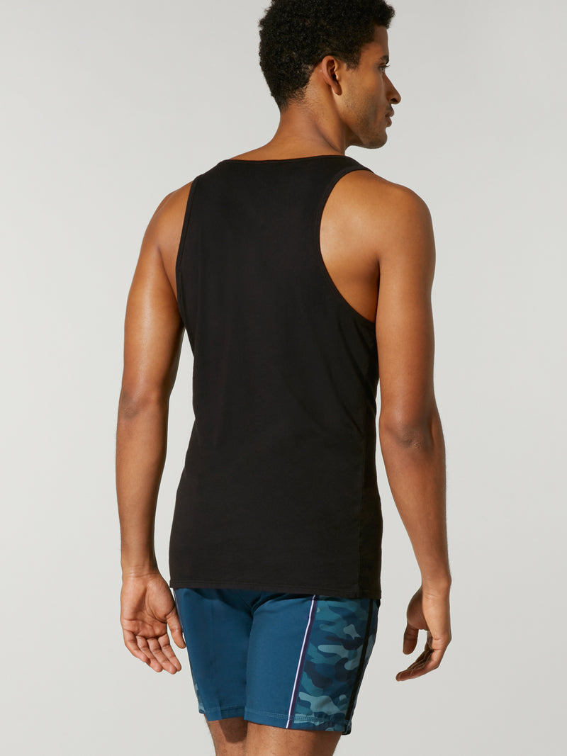 back view of male model in tight black tank top with blue barry's bootcamp logo and blue shorts