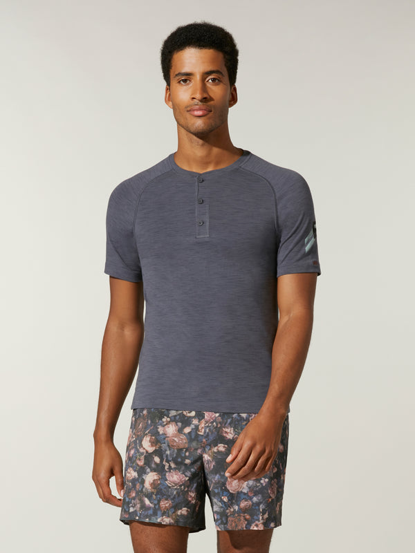 front view of male model in dark grey fitted t-shirt and grey white and pink printed shorts