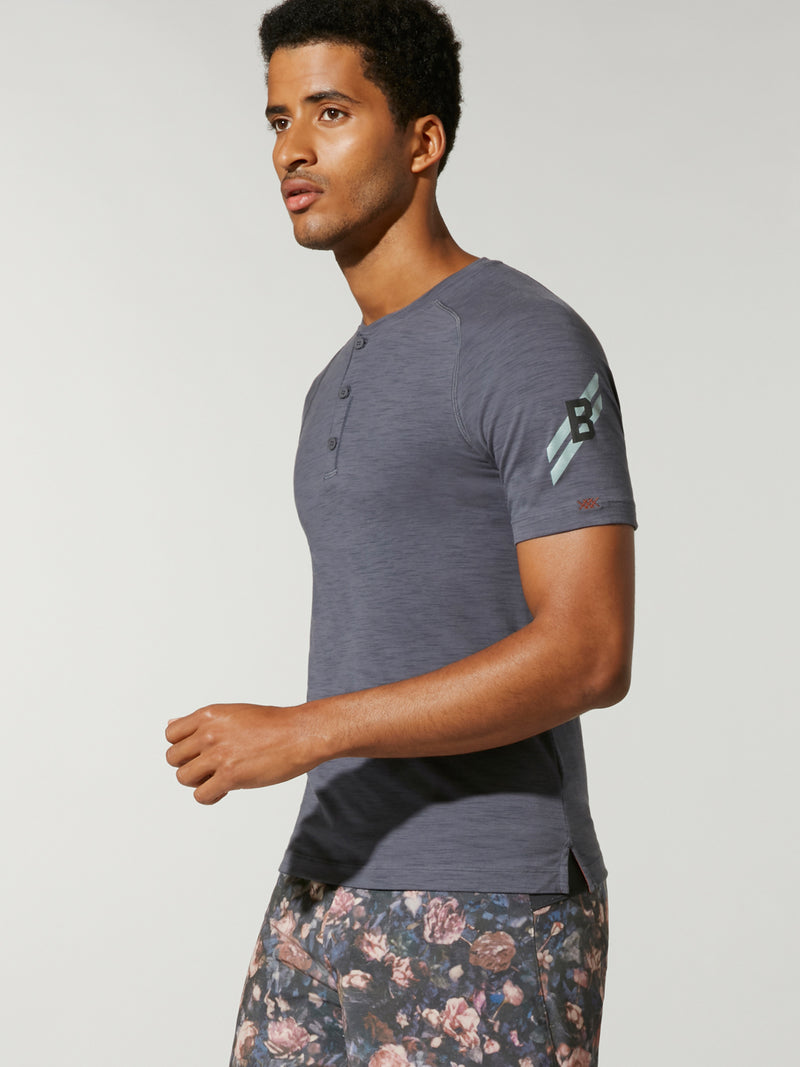 side view of male model in dark grey fitted t-shirt and grey white and pink printed shorts