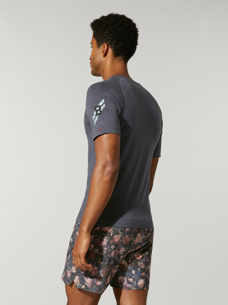 back view of male model in dark grey fitted t-shirt and grey white and pink printed shorts
