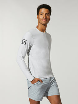front view of male model in white long sleeve workout shirt and grey shorts
