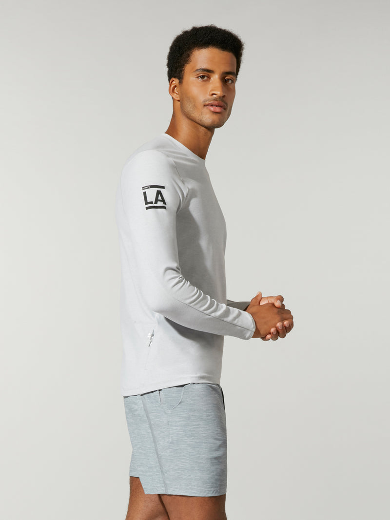 side view of male model in white long sleeve workout shirt and grey shorts