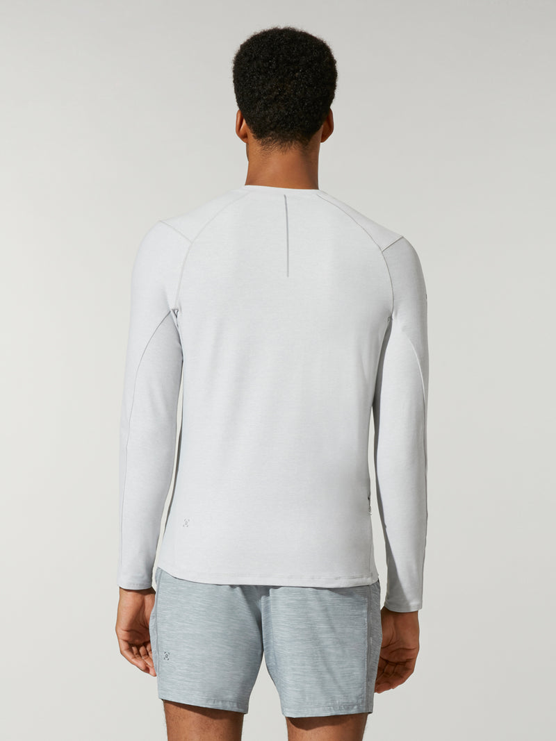 back view of male model in white long sleeve workout shirt and grey shorts