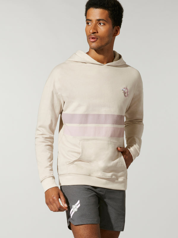front view of male model in sand colored sweatshirt with light purple and light pink stripe across chest and grey shorts