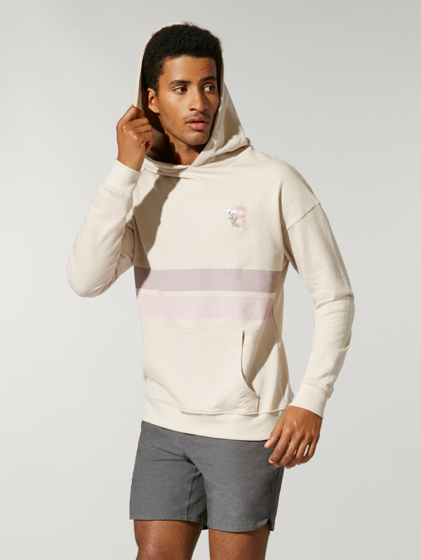 front view of male model in sand colored sweatshirt with light purple and light pink stripe across chest with hood up and grey shorts