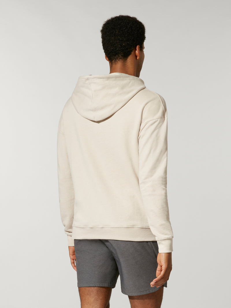 back view of male model in sand colored sweatshirt with light purple and light pink stripe across chest and grey shorts