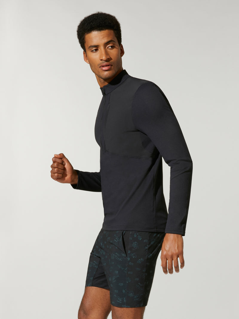 side view of male model in black pullover with three quarter zip and black shorts