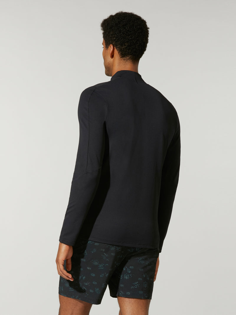 back view of male model in black pullover with three quarter zip and black shorts