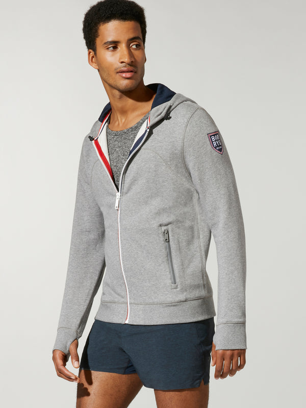 Front shot of model wearing grey FOURLAPS X BARRY'S RUSH HOODIE with barry's logo on right arm