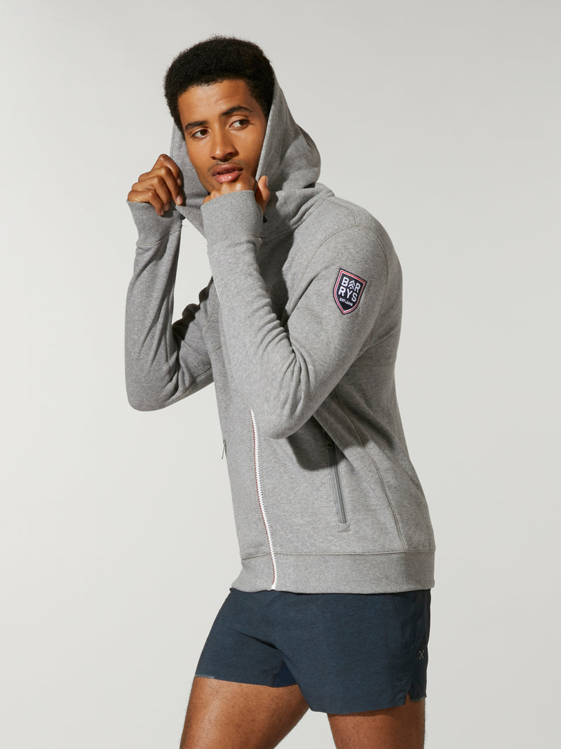 Side shot of model wearing grey FOURLAPS X BARRY'S RUSH HOODIE with barry's logo on right arm