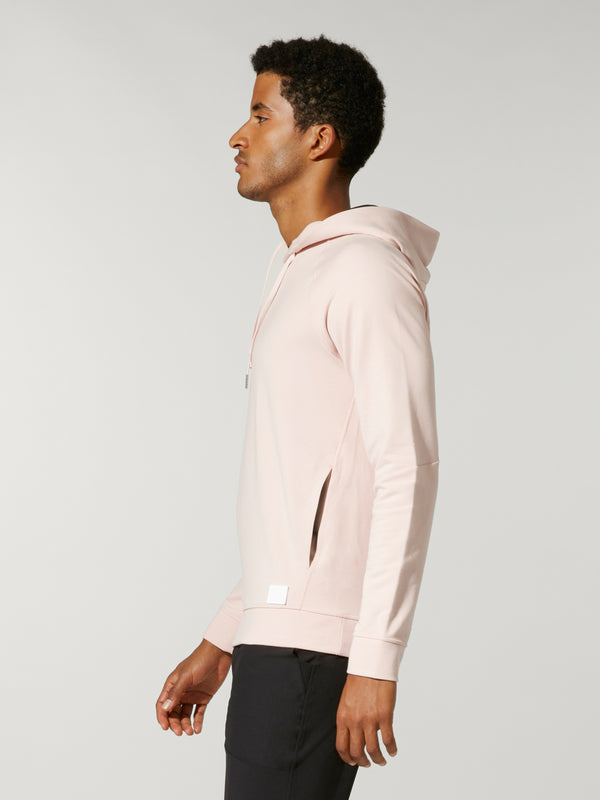 side view of male model in light pink sweatshirt and black shorts