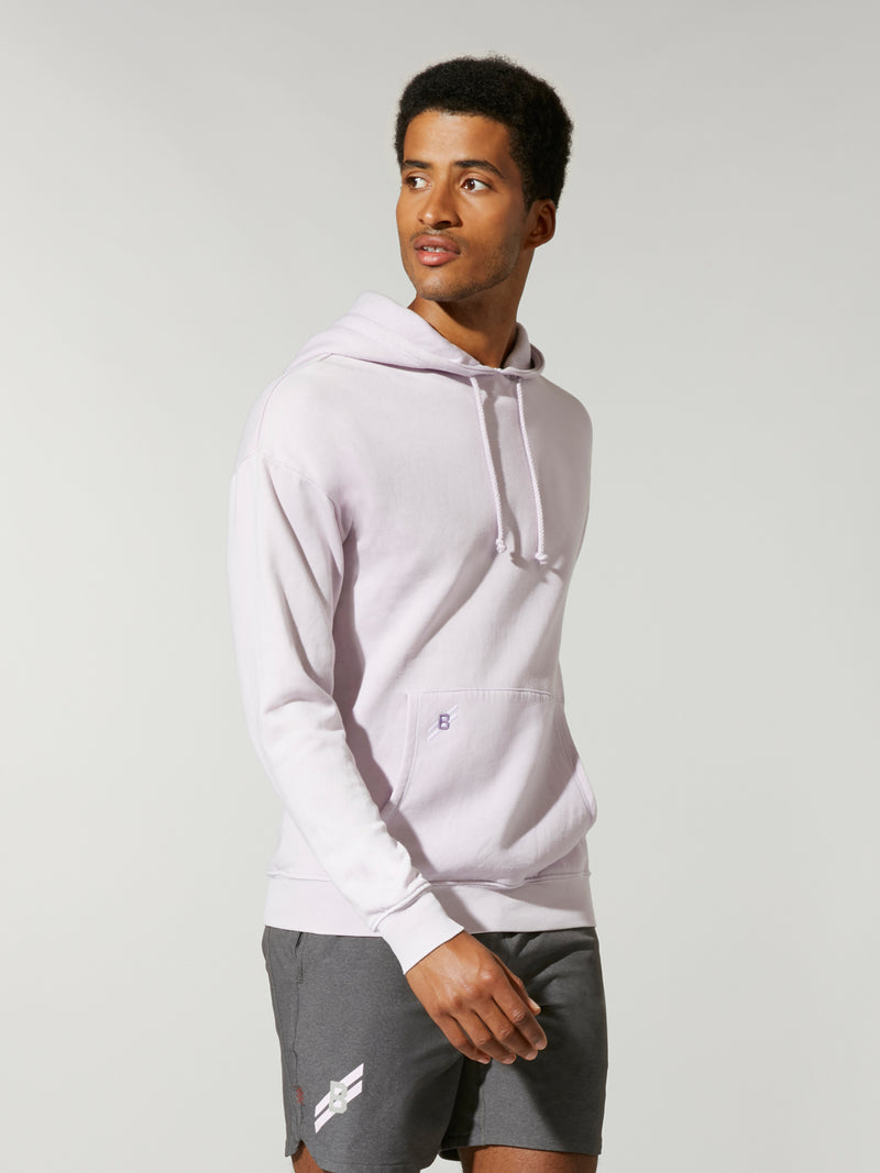 side view of male model in lavender fleece hoodie and grey shorts
